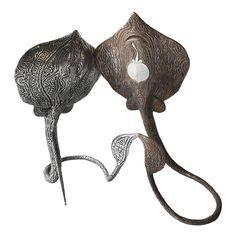 La sculpture de l'artiste aborigène Dennis Nona représente deux espèces de raies pastenagues : la Guuwerr (la raie en bronze) et la Tupmul (la raie en aluminium). Tupmul est le totem de Dennis Nona et l'un des principaux totems de l'ile de Badu.