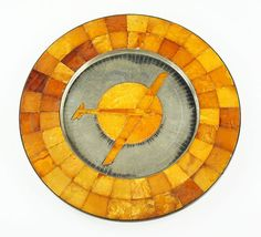 A German Amber and .835 Silver Charger. Round charger is raised on three silver feet underneath. Perimeter of charger is formed by two rows of tapered amber squares. Interior of charger bears engraved lines leading into the center. Center of charger is inlaid with amber depicting a plane in flight across the sun. Reverse bears obscured markings which have been rubbed away over the years. Konigsberg & Staatliche are visible, but the remained is illegible. Charger could have possibly been made…