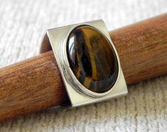 Anel em prata 950 com cabochão de olho de tigre. <br>Tamanho do retângulo 2,4 x 2cm. Número 20.