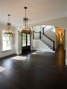 I think dark hardwood floors like this in the foyer hallway and dining room would compliment the carpet and the tiles.
