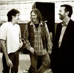 Bob Dylan, Neil Young & Eric Clapton friends sharing a laugh at the Columbia Records anniversary concert.