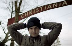"""Lukas Graham posing in front of the entrance to the part of Copenhagen where he was born, """"Christiania"""""""