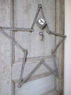 Ancien mètre d'architecte en métal vieilli détourné en étoile.Jolie patine naturelle, l'étoile est agrémentée d'une pampille en papier ancien, jeton et pièce trouée.A poser contre un tableau noir... ou à accrocher au mur...Dimensions :55 x 55 cm