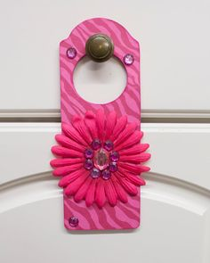 Beautiful, feminine doorknob hanger. Perfect for young ladies. The hanger is adorned with a distressed pink animal print background, gems, and
