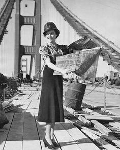 Jane Wyatt holds a blueprint for the Golden Gate Bridge during construction, 1937.