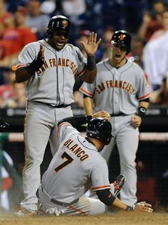 San Francisco Giants' Pablo Sandoval, left, and Buster Posey, right, watch Gregor Blanco score on a Brandon Crawford double that scored three runs in the fourteenth inning of a baseball game on Wednesday, July 23, 2014, in Philadelphia. The Giants beat the Phillies 9-6 in extra innings. (AP Photo/Michael Perez)