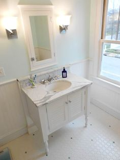 Cottage-style bath - White octagon floor tiles with a scatter of blue dots - Powder blue walls - White beadboard wainscoting - Chrome fixtures - Marble  vanity top