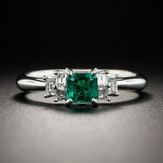 A lovely (.41 carat) vibrant crystalline green square-cut emerald glows between trios of sparkling baguette diamonds in this delightful estate jewel, rendered in gleaming platinum. Currently ring size 6 1/4.