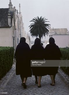 Nazare, Portugal - Three women dressed in mourning black in the Nazare cemetery.