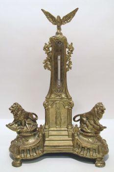Thermometer Zinkguss, goldfarben, in Form eines Denkmals. Mittig im Sockel Darstellung der Freiheitsstatue, darüber Thermometer mit Angaben in Grad Celsius und Grad Réaumur. Bekrönt von einem Adler. Seitlich flankiert von Löwen. H. 36 cm