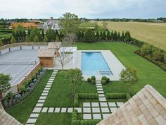 Love the wood lattice fence around this tennis court to keep the homes country charm combined with symmetrical patio pavers and a perfectly rectangular pool to add a modern feel.
