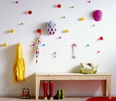 Vestíbulo con tiradores de colores a diferentes alturas, con ropa infantil y accesorios colgando, y un banco con zapatos.