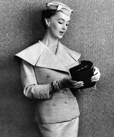 """""""A beige suit of wool, mohair and silk with an oversized collar lapel by Jean Desses, bag and gloves by Hermès, 1955."""""""