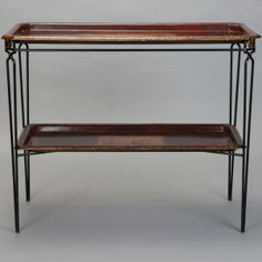 French Two Tier Console with Metal Base and Tole Trays --- French two tier table has a black metal frame with tapered legs and gilded medallion accents at the corners. Table tops are removable tole trays with gilded borders with central scenes of people and flowers. ---  Item:  4149 --- Retail Price:  $4149