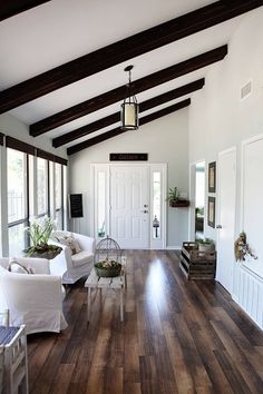 hard wood floors, white walls, and dark beams. Not crazy about the slip covered chairs though