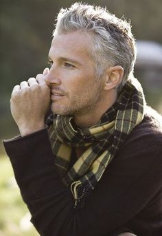 """Traditional plaid scarf casually worn with sweater.  Great windblown hair and light beard on the """"silver fox""""."""