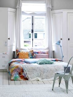 white room, colourful bed