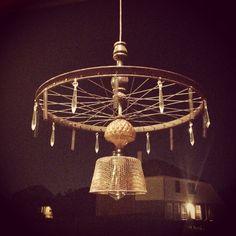 Repurposed chandelier.  Bike wheel, old chandelier, springs and crystals, and a vintage fry basket...  Www.facebook.com/DEAndLShop