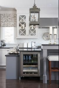 Absolutely beautiful kitchen cabinets painted a soft gray - Para Paints Shoreline, kitchen island painted a deep gray/blue in Para Paints Herringbone with drop down cabinet & wine fridge with honed black countertops, Sarah Richardson Jake Counter Stools upholstered in Kravet Dotkat Mineral Fabric, kitchen island pendant from Of Things Past, custom roman shades in Kravet Sanabelle Driftwood fabric, marble mosaic fish scale tiles backsplash from Saltillo Tiles.