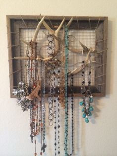 Jewelry rack.  Old wooden frame, wire (chicken wire or similar), deer antlers and a mom. Ta-Daahhh!