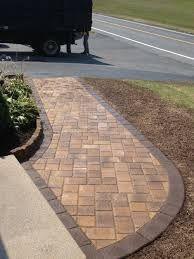 This patio combines concrete pavers in different sizes and shapes to create an interesting random pattern. While the main part of the patio uses light-colored pavers, the darker-pavers-designed edge is for a contrasting appeal.