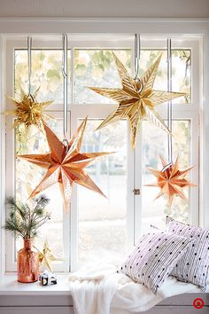 It's easy to add holiday glam, even if your space is on the neutral side. Metallic paper star lanterns in a mix of sizes will feel just as celebratory hanging in a window in the living room as they will above a holiday dinner table. (We kept the minimal feel going by pairing the stars with black-and-white striped ribbon from our Sugar Paper for Target collection.) And they work for day or night—let the sun shine through or light them up with a simple light cord.