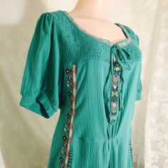 Teal dress 100% cotton dress with stretchy area in the sleeves and in the bust. A great print accents the beautiful teal fabric. The dress has pockets, and it ties in the back. 35 inches long.   Teal dress Spring Trends HOST PICK 3/21/2016 Maribelle Dresses