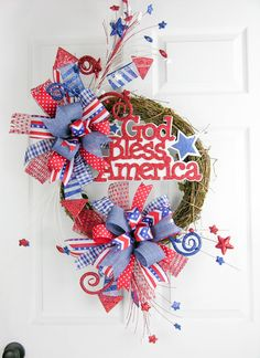 """This is a simple design with two Terri Bows filled with patriotic ribbons and rocket starred glitter stems. A God Bless America sign pays tribute to our great country. Measures 40""""H X 22""""W."""