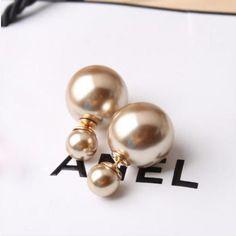Top trendy Dior-inspirerede øreringe med champagnefarvede dobbelte perler. Stikken er fremstillet af forgyldt nikkelfri kirurgisk stål. Den store perle måler ca. 15 mm. Den lille perle ca. 8 mm. Ørestikkerne fås i flere farver og varianter - se de øvrige