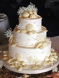 bridal shower cakes beach theme | Three tier ivory wedding cake decorated with white chocolate seashells ...