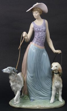 "LLADRO PORCELAIN FIGURE ELEGANT PROMENADE 5802  Lladro Spain porcelain figure Elegante Promenade #5802. Spanish Name: Dama Con Perros. Glazed Finish. Sculpted by Regino Torrijos. Issued in 1991. Current Retail price of $1,000.00. Measures 15 1/2"" height (39.3cm)."