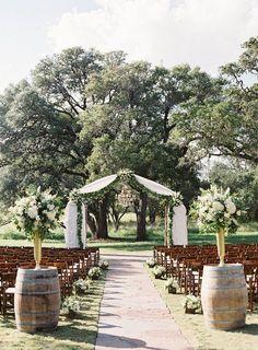 Outdoor wedding ceremony decor - white fabric + greenery ceremony arch with wine barrels {Ma Maison} #weddingdecoration
