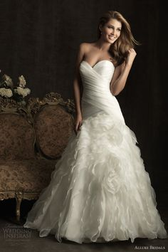 A-line wedding dress with fitted strapless, sweetheart bodice that is ruched asymmetrically. The dropped waistline continues into a dramatic ruffled organza skirt.