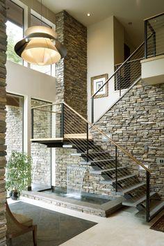 moderne treppe natursteinwand holz geländer brunnen innen