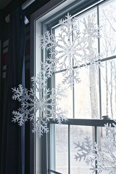Dollar store plastic snowflakes hung with fishing wire from the curtain rod... Easy (& cheap) Christmas decor