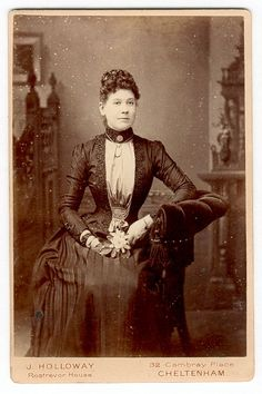 1880s cdv- very elegant dress, shirred at the bottom of the bodice, lots of beaded trim along front and sleeves, wearing a chain at her neck with a pendant, brooch at neck and two chains down by the shirring. Very tiny single drop bead earrings.