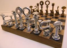 Nuts and Bolts Chess set. Full set of dark and light finished pieces. The hand painted board is 8×8 inches with a 8×8 playing area. The Board features a black and gray DISTRESSED finish.