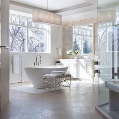 White and gray bathroom features a gray rectangular pendant hanging over a modern freestanding tub and a black and white silver faux bois bench and a sleek freestanding towel warmer placed under windows.