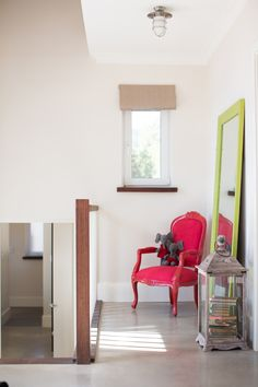 books in lantern.  chair with red frame and upholstery.  lime green frame around floor mirror.