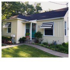 Three different styles of new Mastic vinyl siding in Classic Cream. Black and white striped aluminum awnings from General Awnings. Love love love my little house makeover!