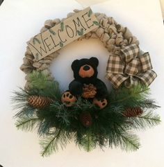 Adorable Burlap Wreath with Black Bear, Welcome Sign, Pine Branches and Pine Cones  Beautiful wreath with natural color burlap  Plush black bear with brown paws  Assorted types of pine and evergreen branches and pine cones  Hand painted wood sign Welcome painted black  Approximately 20 inches  Made in a smoke free home.  Ready to ship!  Recommended for indoor use only.