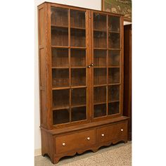 Impressive 1800s medical cabinet used by two generations of doctors from the same family. Features fixed shelves behind glass-inset double doors, paneled sides, and two bottom drawers for additional storage. Finished with a decorative carved skirt. Doors and hardware are all original.