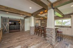 This Iowa mansion has two kitchens, including a rustic dining area near a home theater complete with barn doors. Stone details, hardwood floors and white cabinets complete the look. West Des Moines, Island Beach, Heartland, White Cabinets, Home Theater, Barn Doors, Dream Homes, Dining Area, Iowa