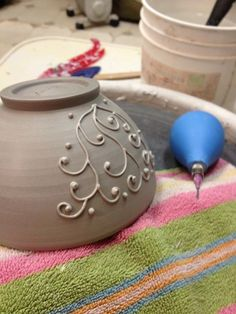 Slip Trailing - a technique that involves working with ceramic pieces that are in a leather-hard state and slip (liquid clay with a paint-like consistency) is applied with a squeezable bottle or bulb with a variety of nozzles. Can create delicate surface designs that won't run the way glazes will, and adds a 3-dimensional quality.    ©PotteryByLisa
