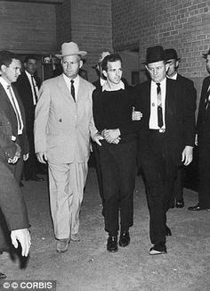24 Nov 1963, Dallas, Texas - Jim Leavelle (left) escorts Lee Harvey Oswald during a press conference two days after his arrest in conjunction with the assassination of President Kennedy