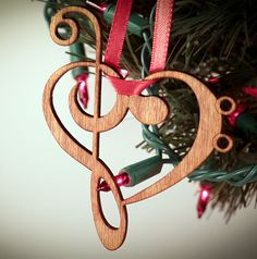 This special Christmas ornament uses a treble clef and a bass clef to make up a heart. This is a great gift for those that play instruments or love music. Its made of Baltic birch and is laser cut and engraved. The birch plywood is 1/8 thick. It comes on a ribbon usually white, red, or green. Its stained and sure to last a lifetime.  It measures roughly 4.9 inches tall by 3.8 inches wide. A great stocking stuffer.  See the bass clef version at…