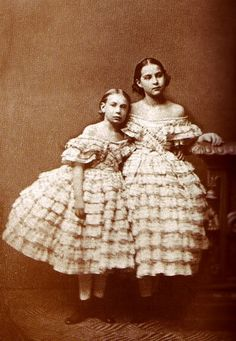 Grand Duchesses Vera and Olga of Russia.  They were two daughters of Grand Duke Nikolaevich of Imperial Russia and his wife Grand Duchess Alexandra, a princess of Saxe-Altenburg.   They are dressed here for a very elaborate social occasion in ruffles, ruffles, and more ruffles.