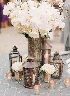 Centro de mesa combinando flores naturais, gaiolas, lamparinas e velas.