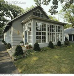 SUNROOMS: Front of small grey stucco bungalow, addition of sunroom, border garden along house with shrubs and flowers, - forthehome