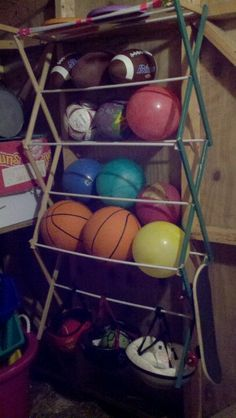 Clothing drying rack turned into kids sports storage.